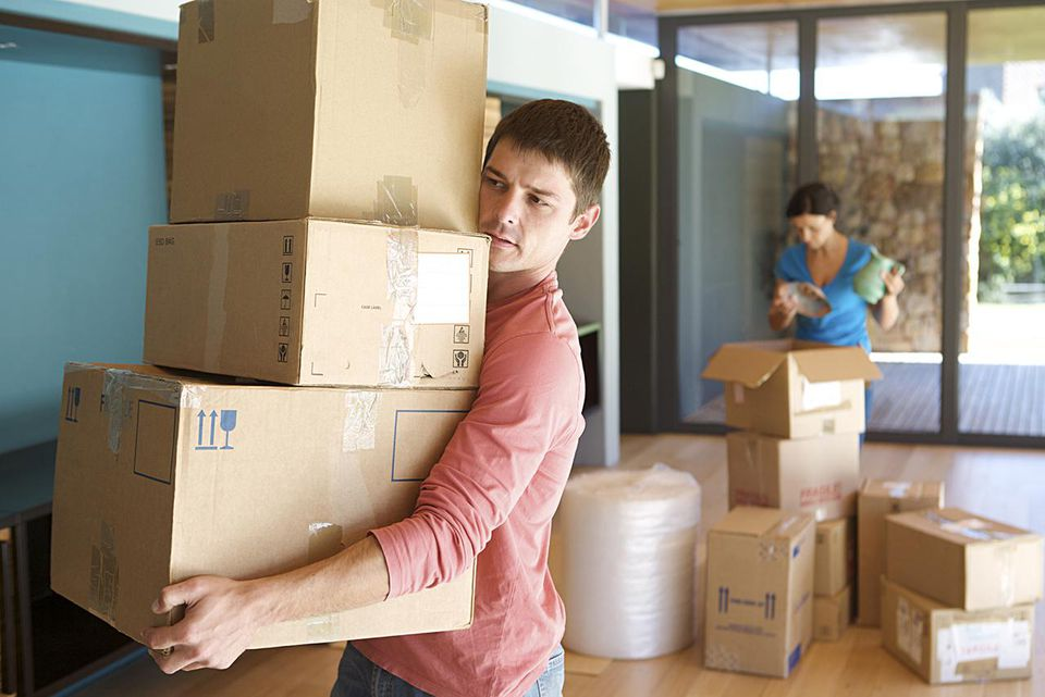 Man carries packed moving boxes while a woman continues to pack boxes