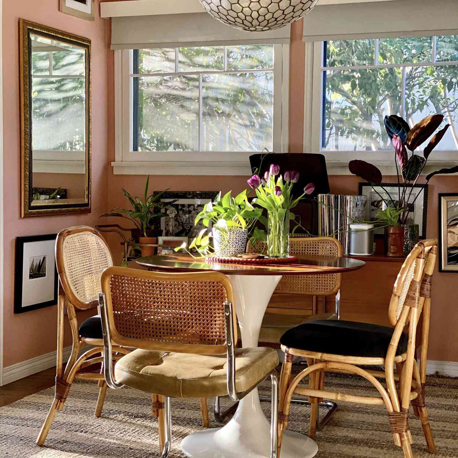 dining room corner with pink walls and abstract gallery wall