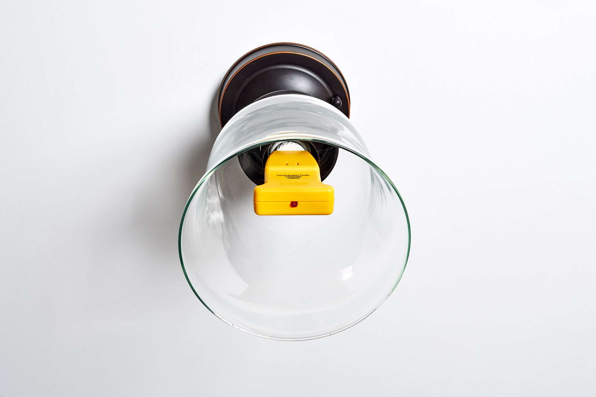 Circuit breaker finder inserted into light fixture with adapter