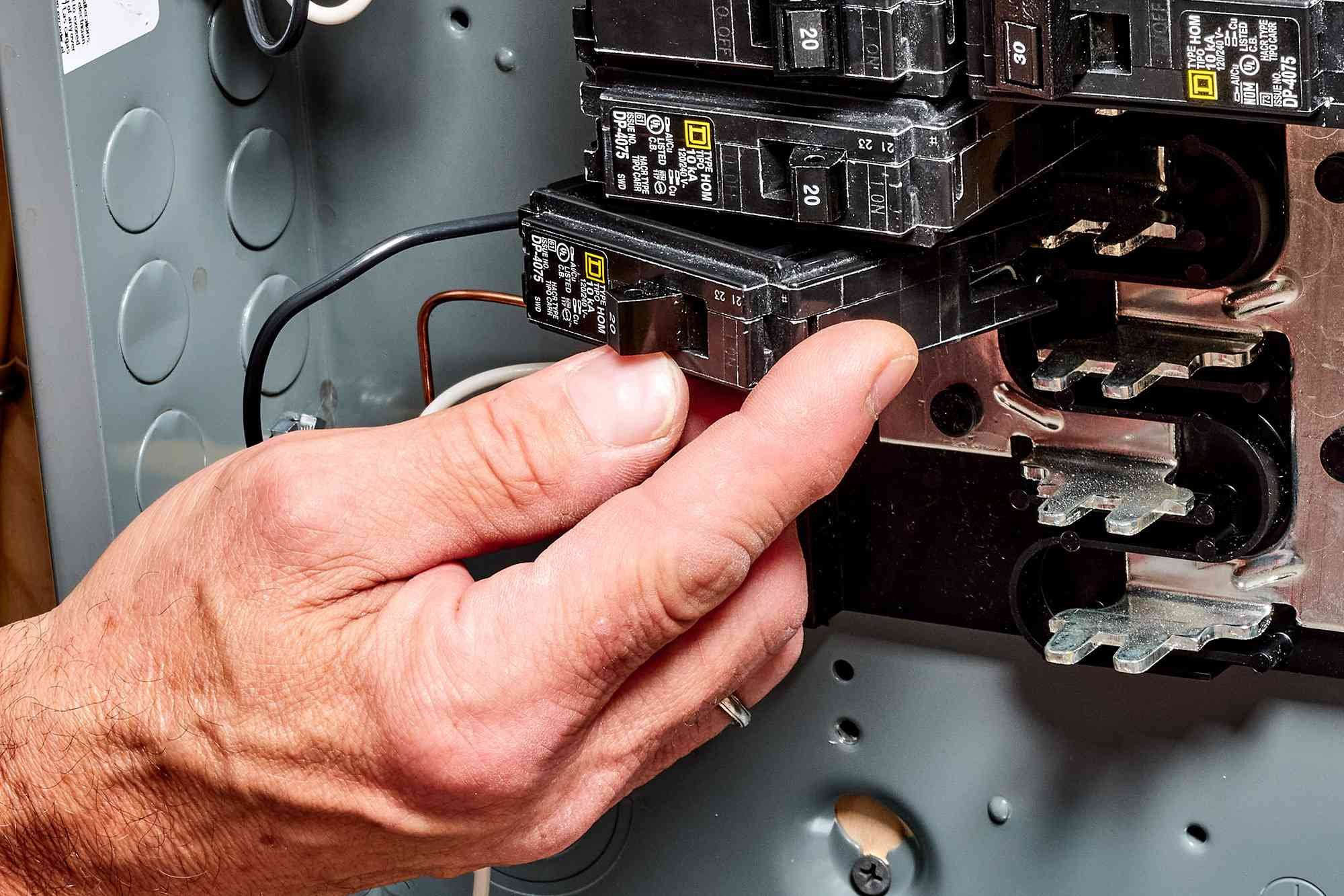 Circuit breaker being replaced inside service panel