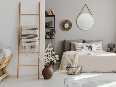 Scandi open space bedroom interior with double bed with knit blanket and many pillows, rack with books and decor, carpet on the floor in real photo