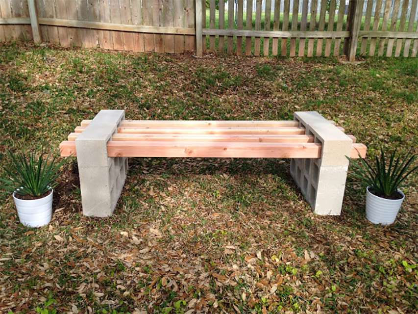 A cinder block and wood bench out in a yard