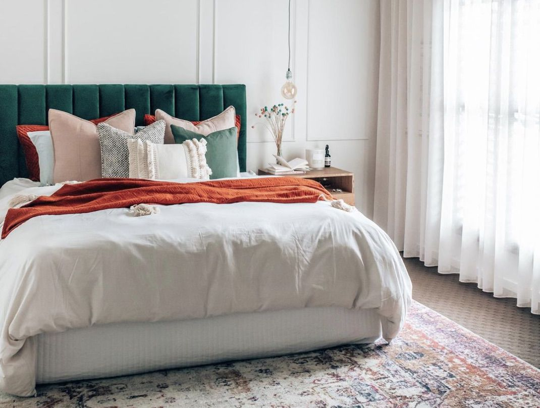 scandinavian style bedroom with burnt orange, dark green, and patterened accent rug