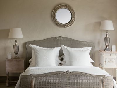 Gray bedroom with bed, two end tables, two lamps, and a mirror over the bed.