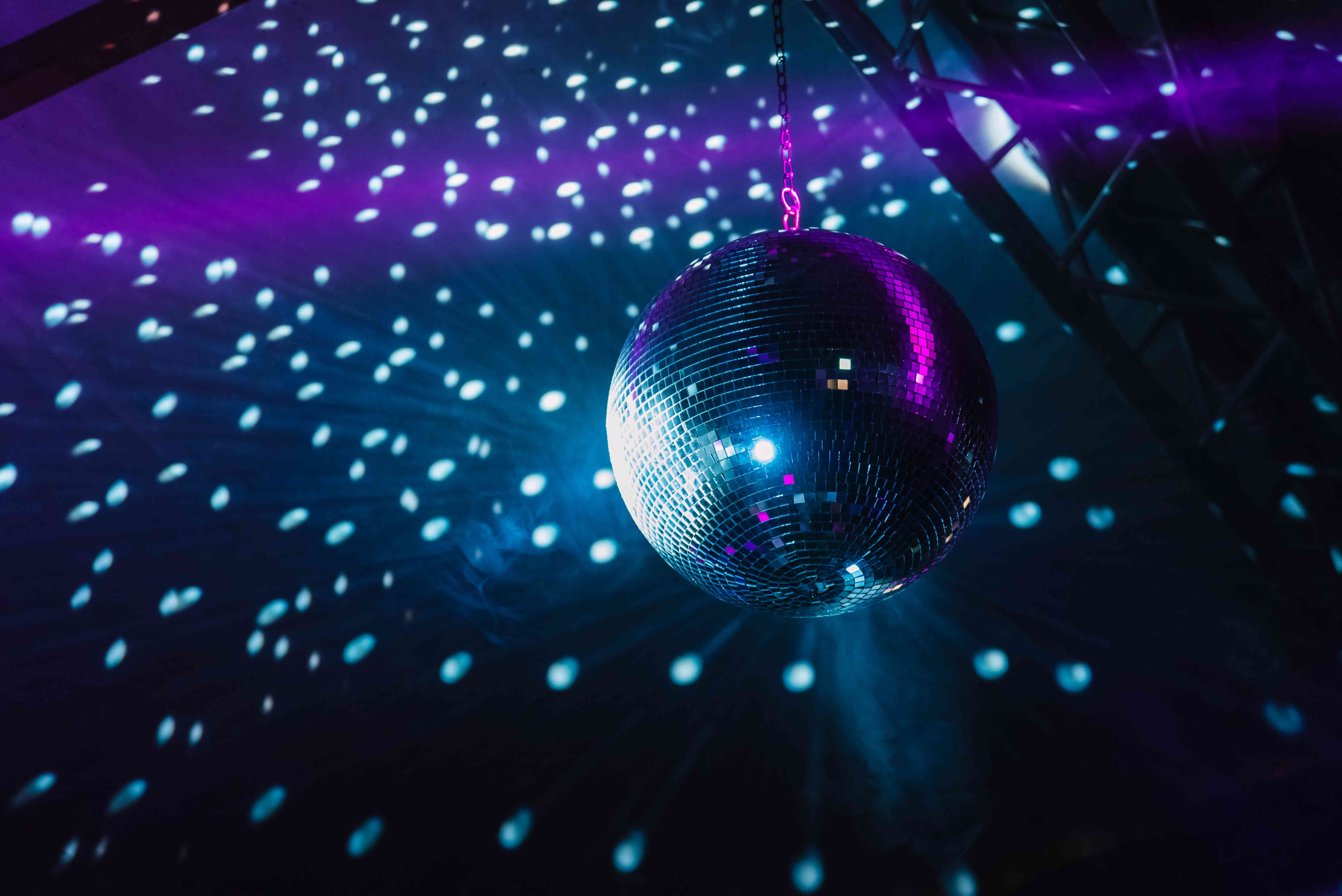 Low Angle View Of Illuminated Disco Ball Hanging On Ceiling In Nightclub