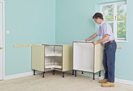 man positioning kitchen units against a corner of a room next to a window - Kitchen Cabinets Cost