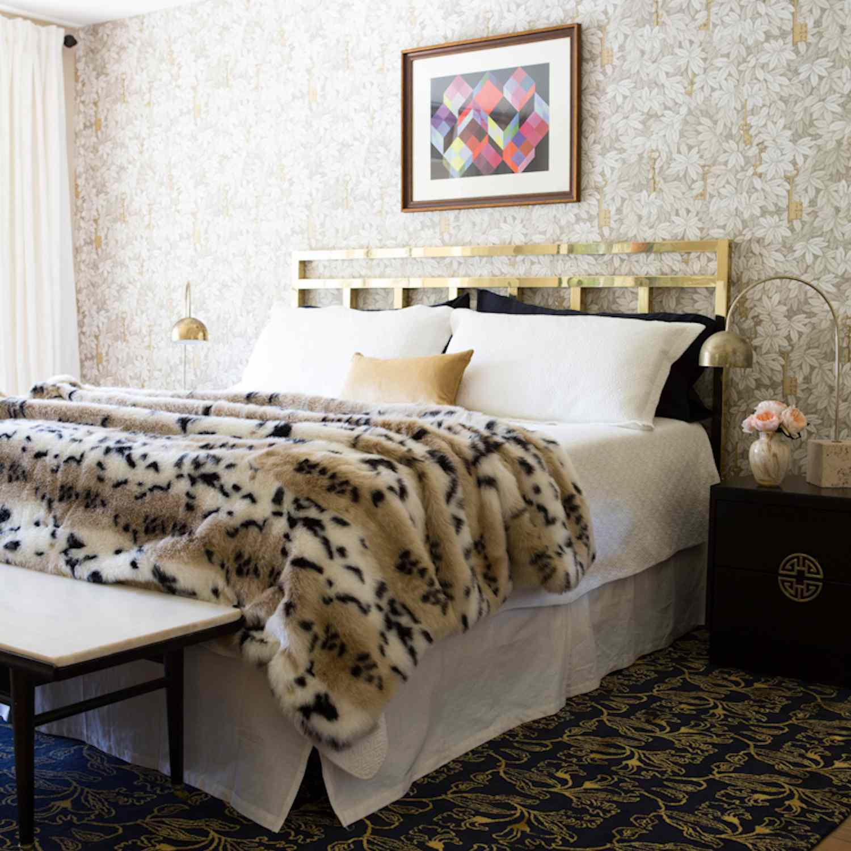 modern bedroom with leopard print fur blanket, golden headboard, tan and beige accents, glam