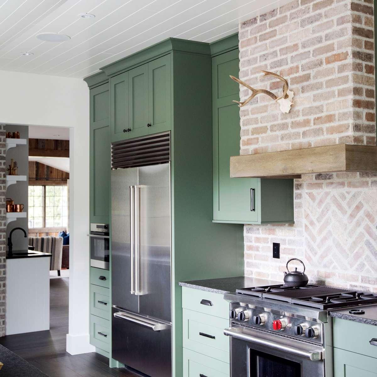 Green kitchen cabinets with brick backsplash