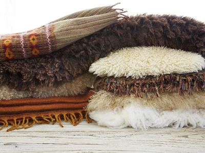 Still life of wool Tibetan blankets, pillows, and pelt rugs on wood table