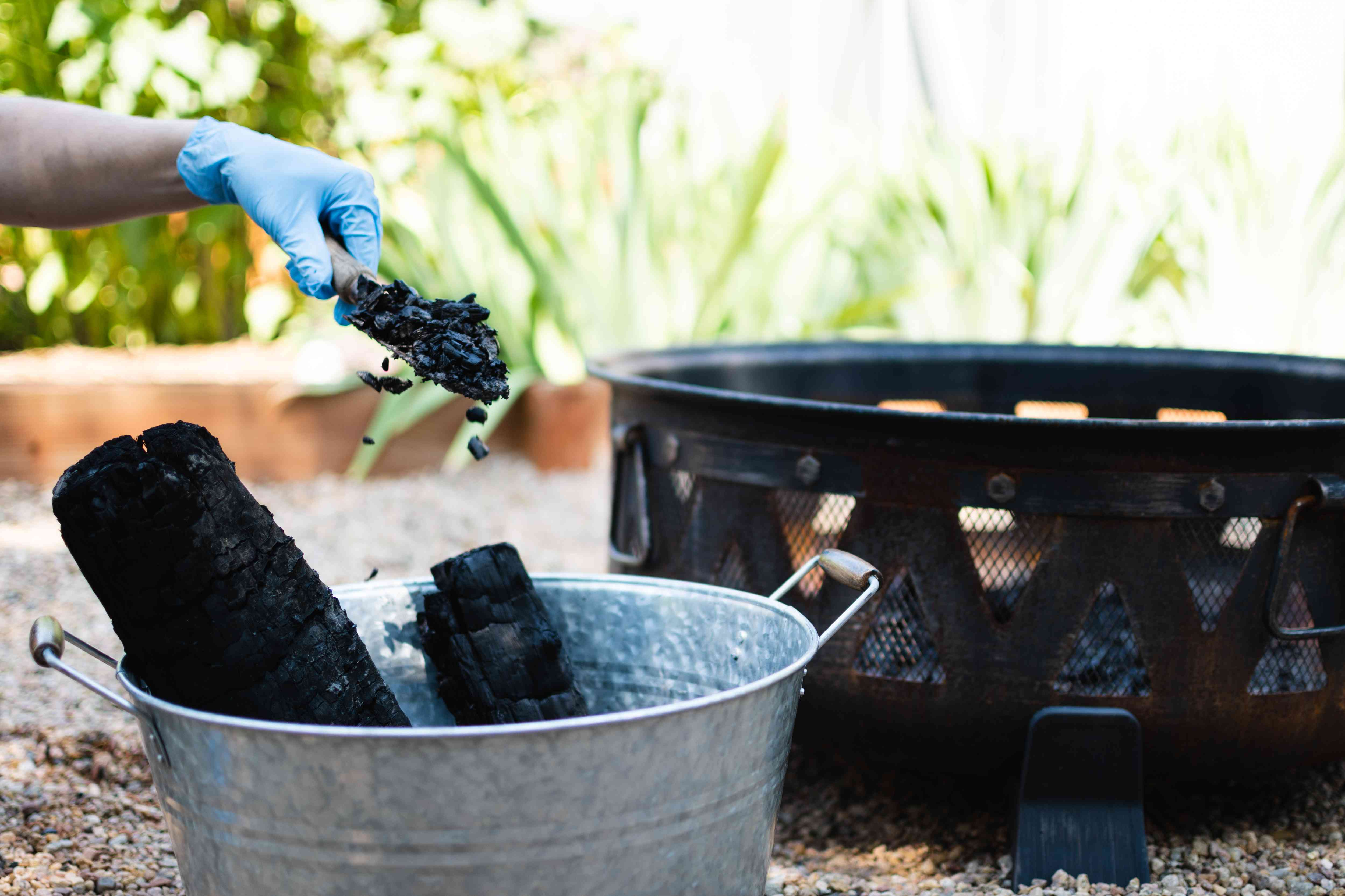 Ashes being removed from metal fire pit and placed in steel bucket