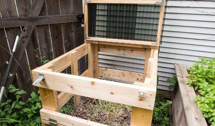 A wooden compost bin outside a house