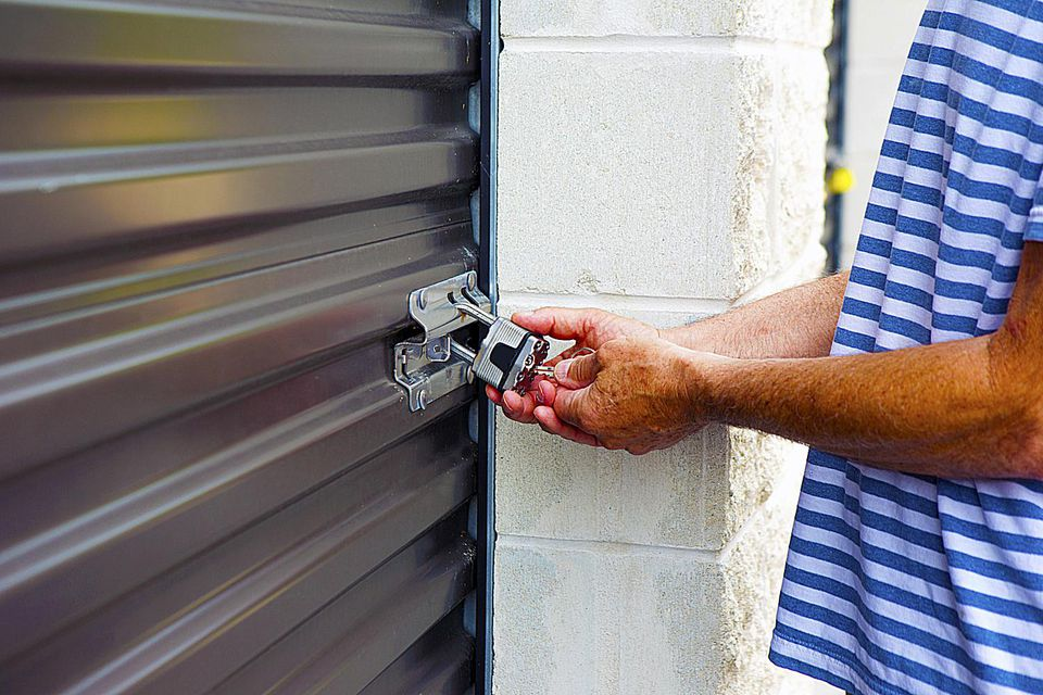 A man turning a key on a storage locker's lock