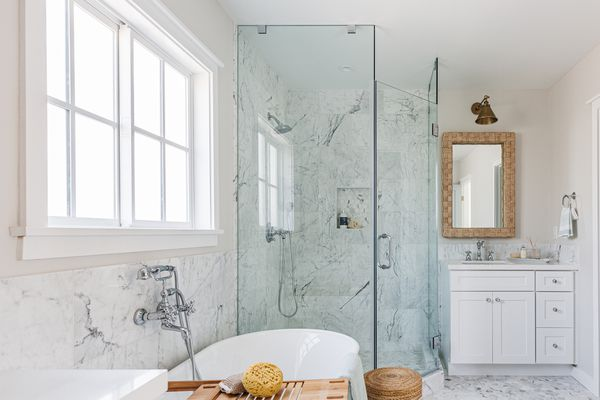 Glass shower door in white marbled bathroom with white tub and large window