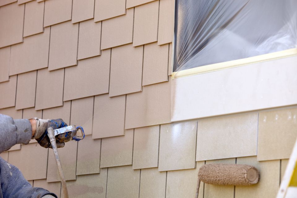 A house painter spraying paint on new siding