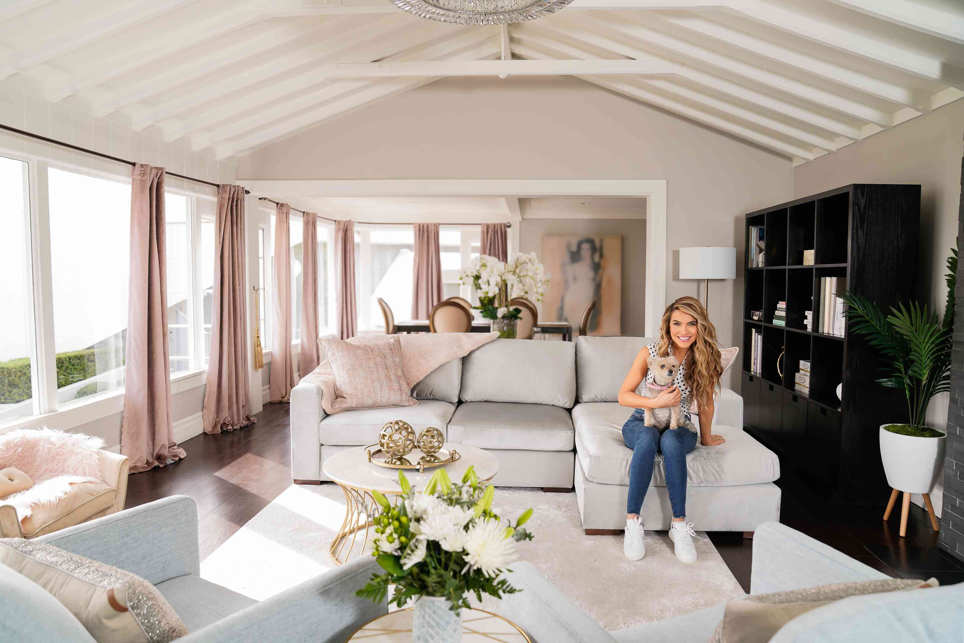 Chrishell Stause poses with her dog in her newly redecorated living room that features updates from TJMaxx and Marshalls