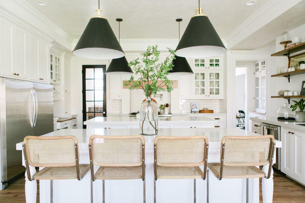 gabinetes de cocina blancos, sillas de canasta y lámpara colgante verde