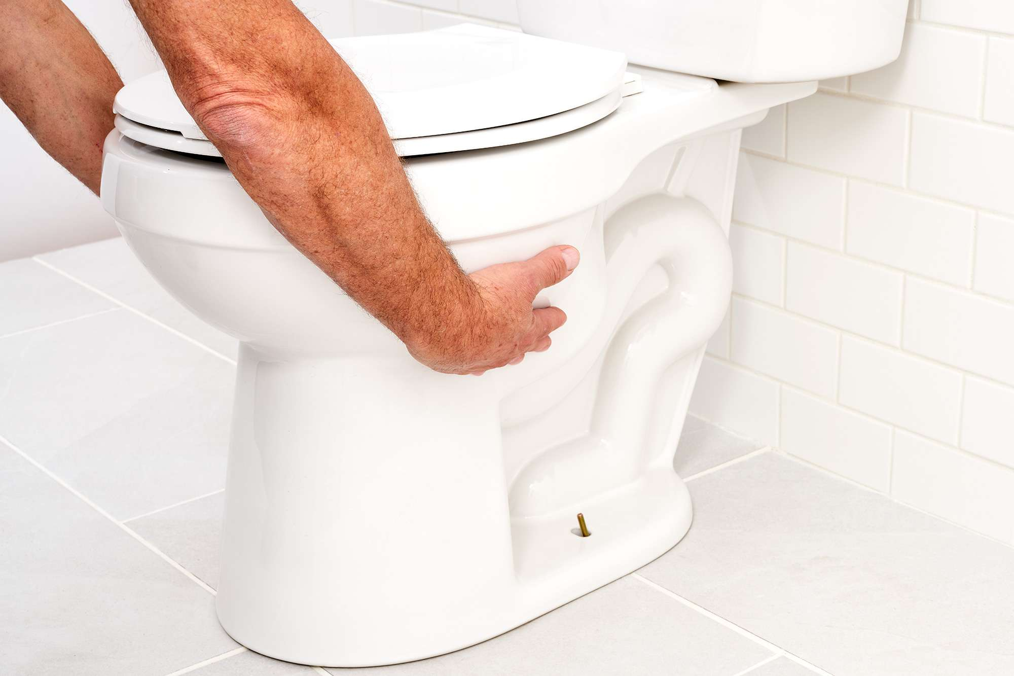 White toilet lifted by straddling toilet bowl on both sides