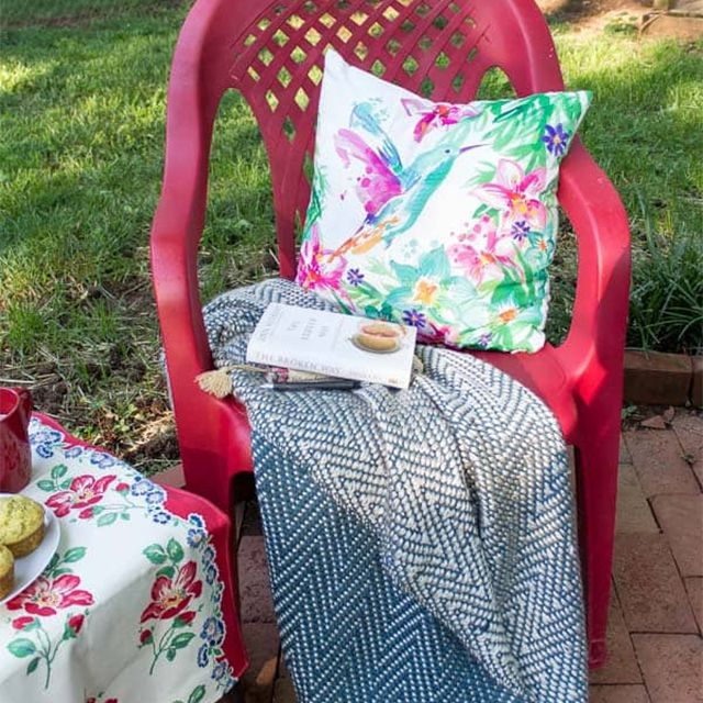 A red plastic chair with a pillow and blanket