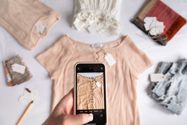 person photographing clothing on their phone