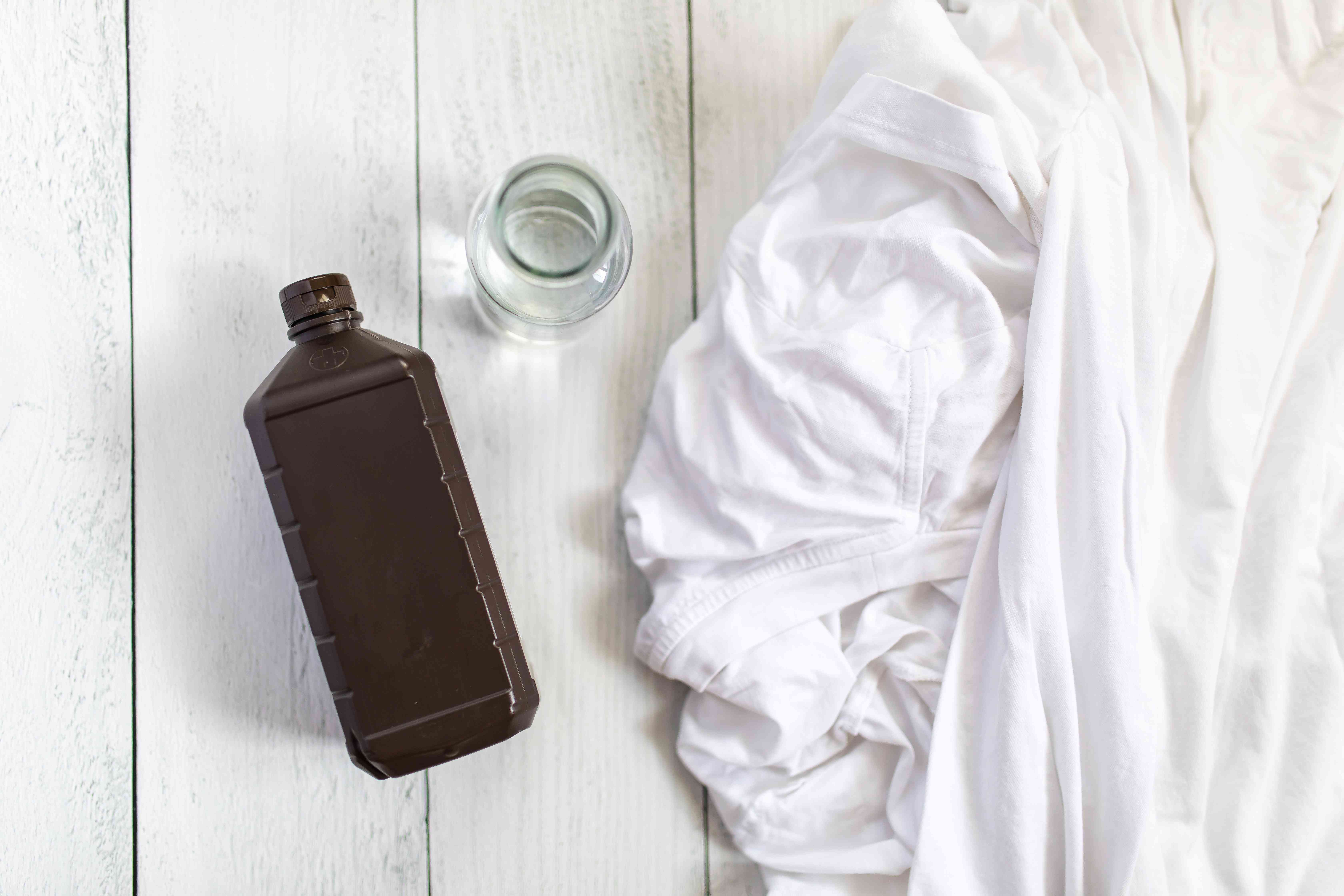 bottle of hydrogen peroxide next to white clothes