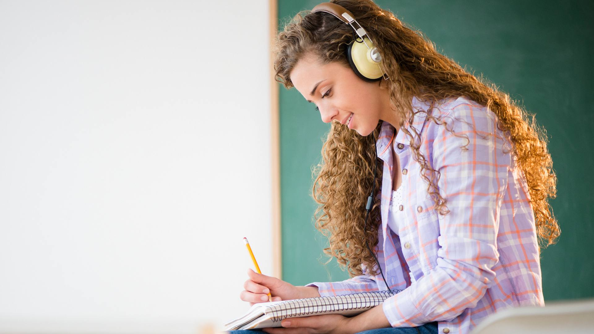 Female student studying with noise-cancelling headphones on