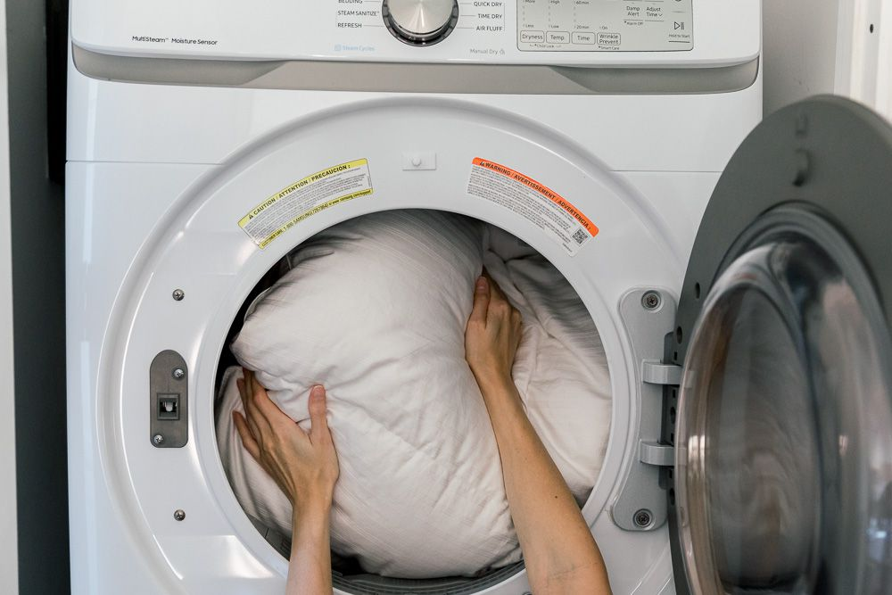Someone loading a white comforter into a dryer