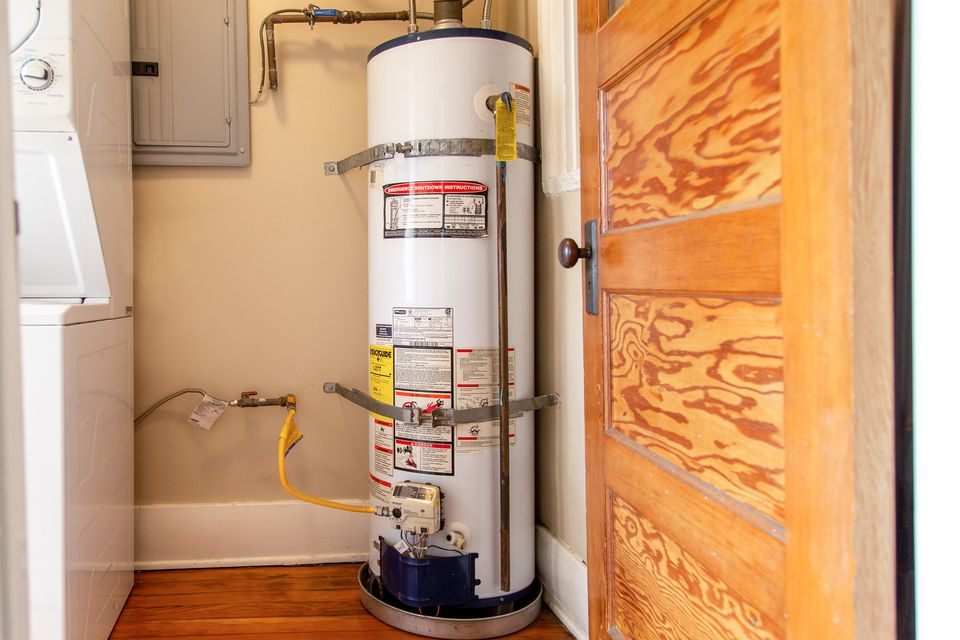 Water heater tank in room corner next to laundry machines and wood door
