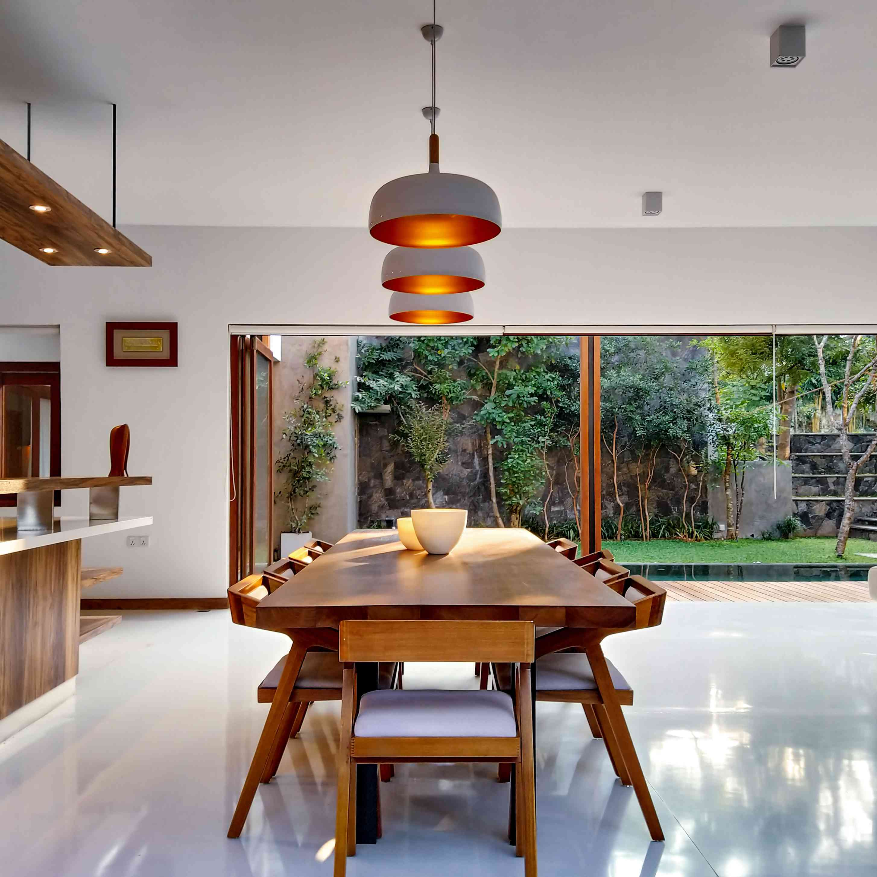 dining room with large wood dining table and white floor and walls