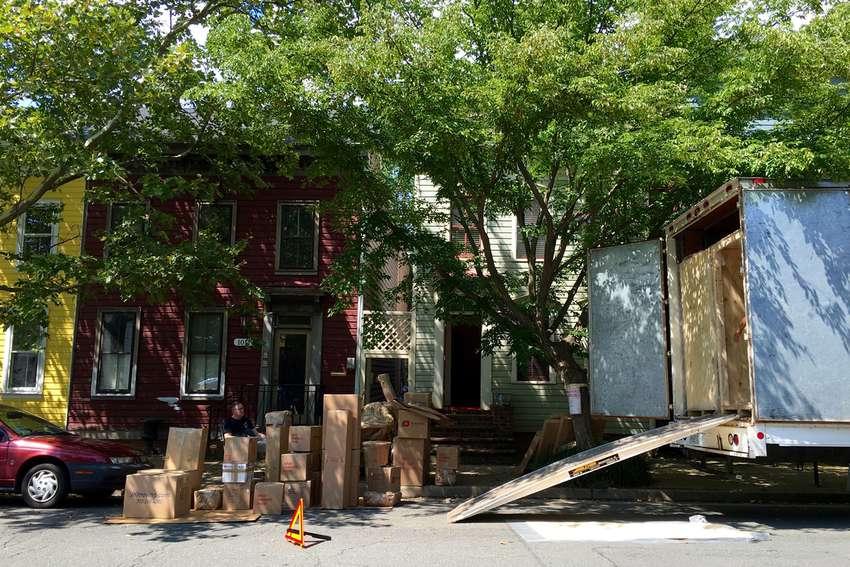 Boxes on sidewalk by moving van in residential neighborhood