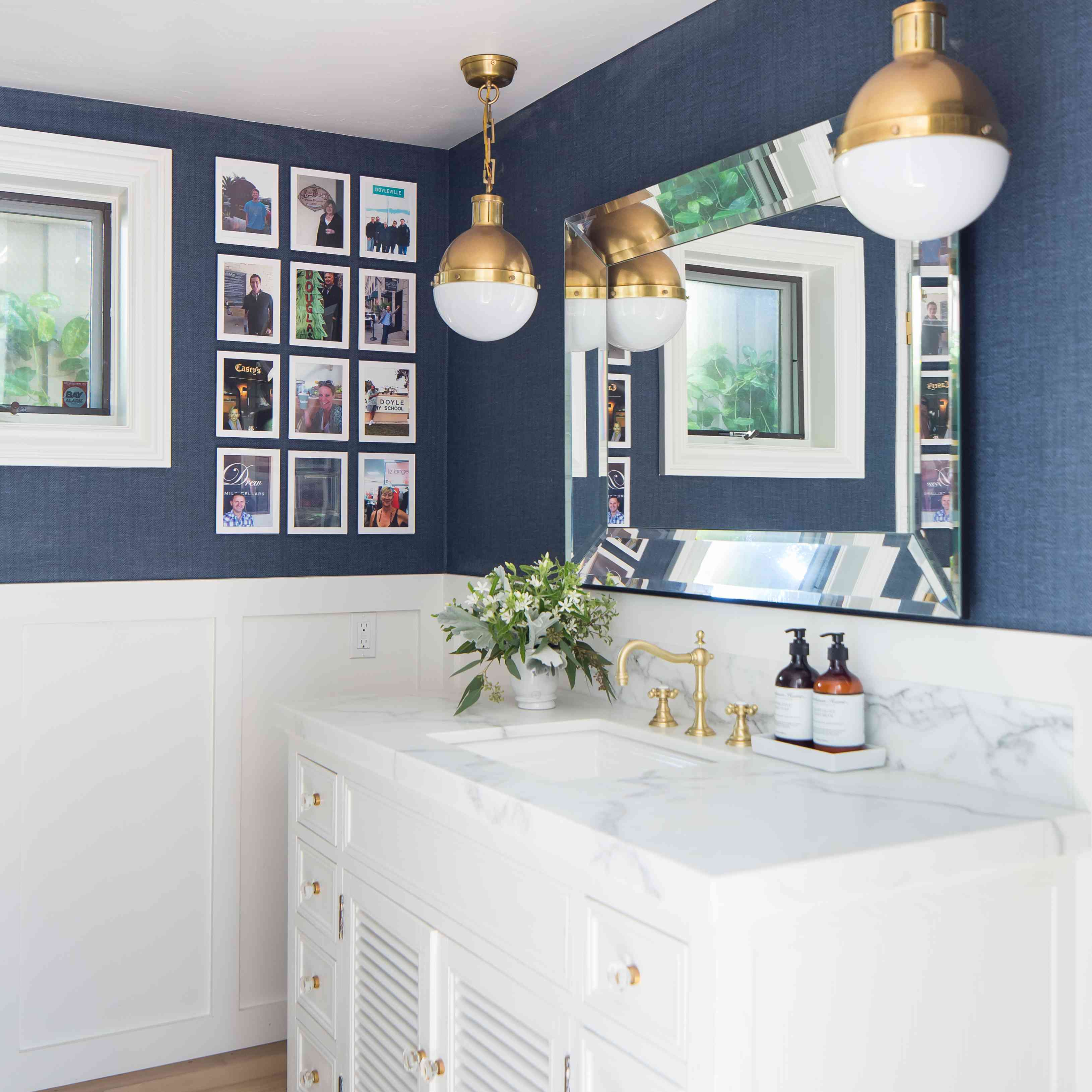 nautical blue and white bathroom with brass lights