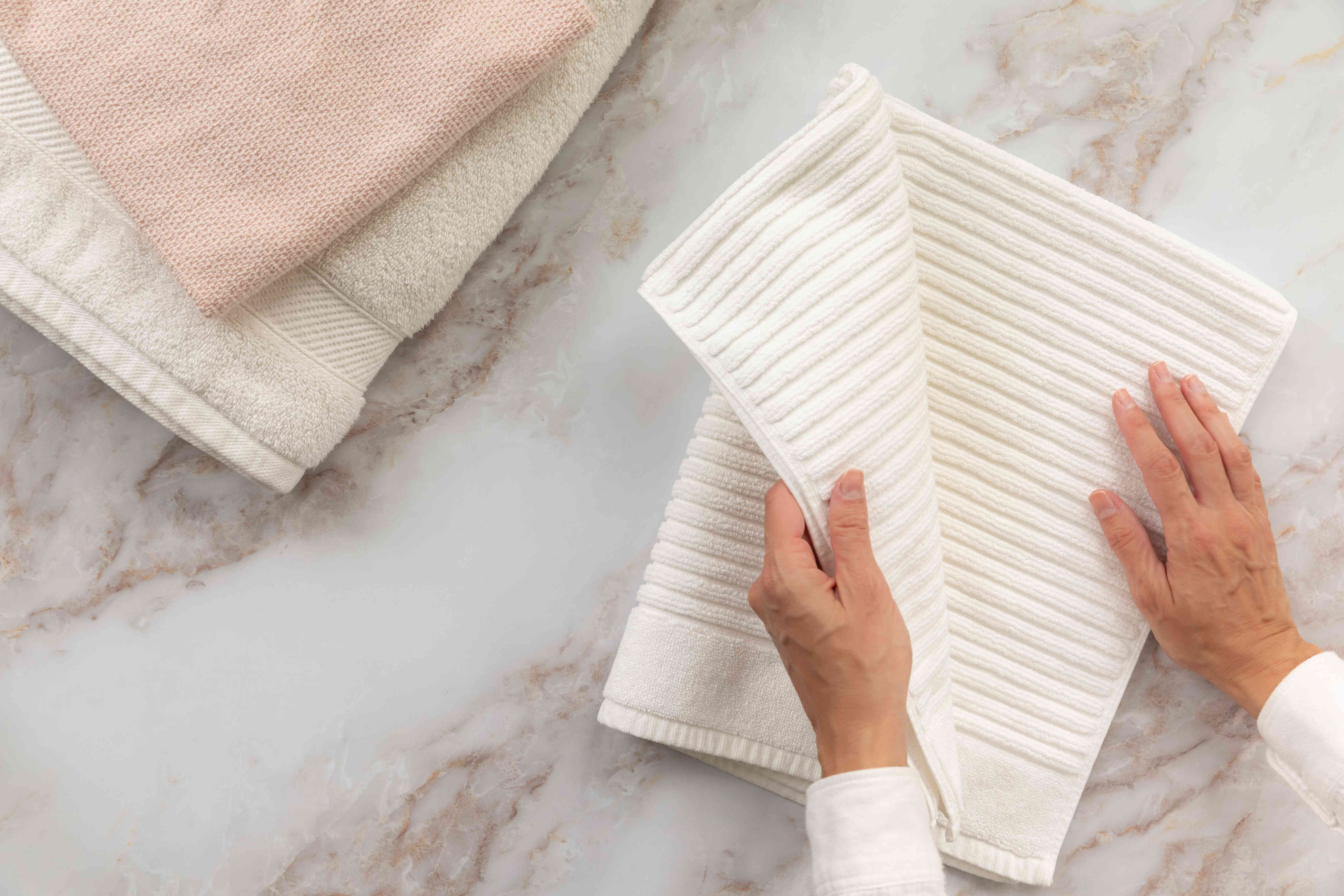 White ribbed bath towel folded in half twice next to other bath towels
