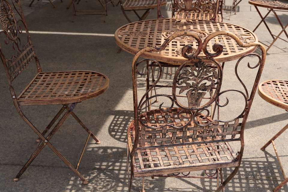 Vintage brown rusty metal table and chair outside