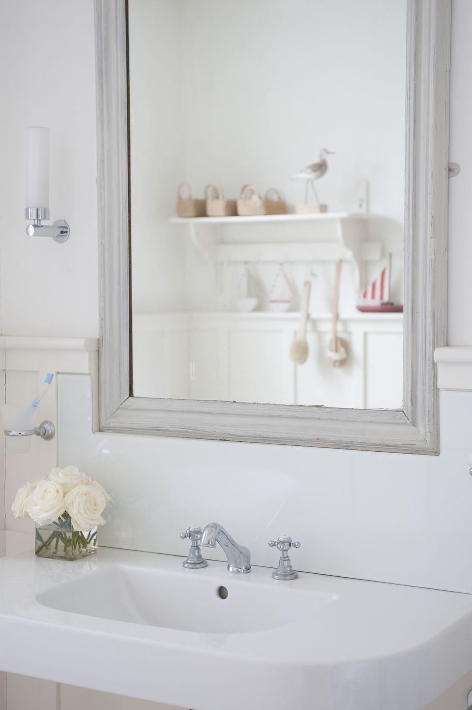Grey painted mirror surround above washbasin, London
