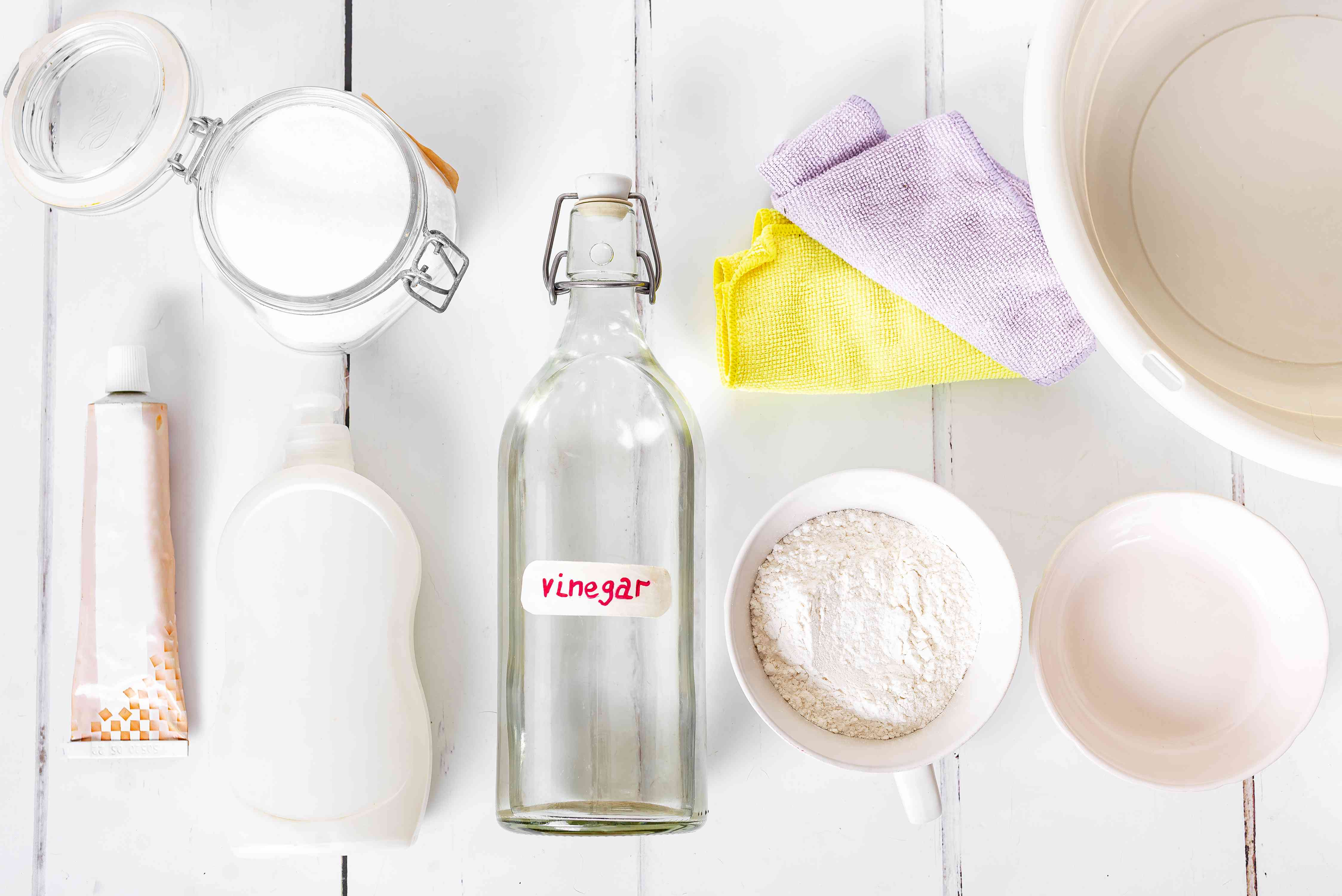 Materials and tools to clean pewter items on white wooden surface