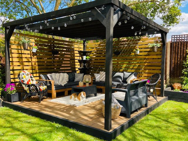 A covered patio features hanging string lights, horizontal slat privacy fence, and a rug