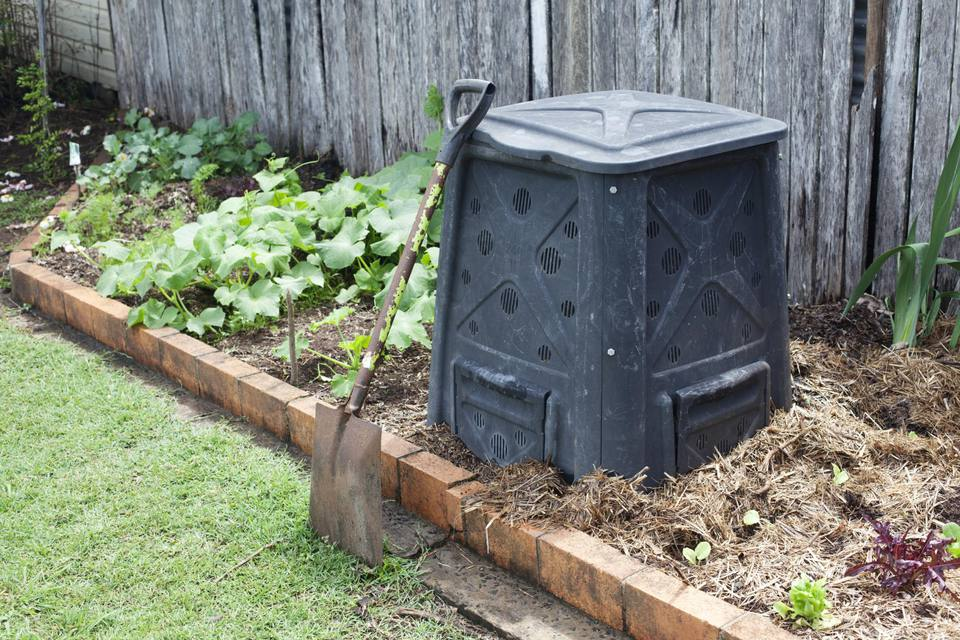 Compost bin in a backyard vegetable garden