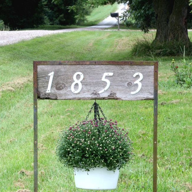 A wooden house number sign with a hanging planter.