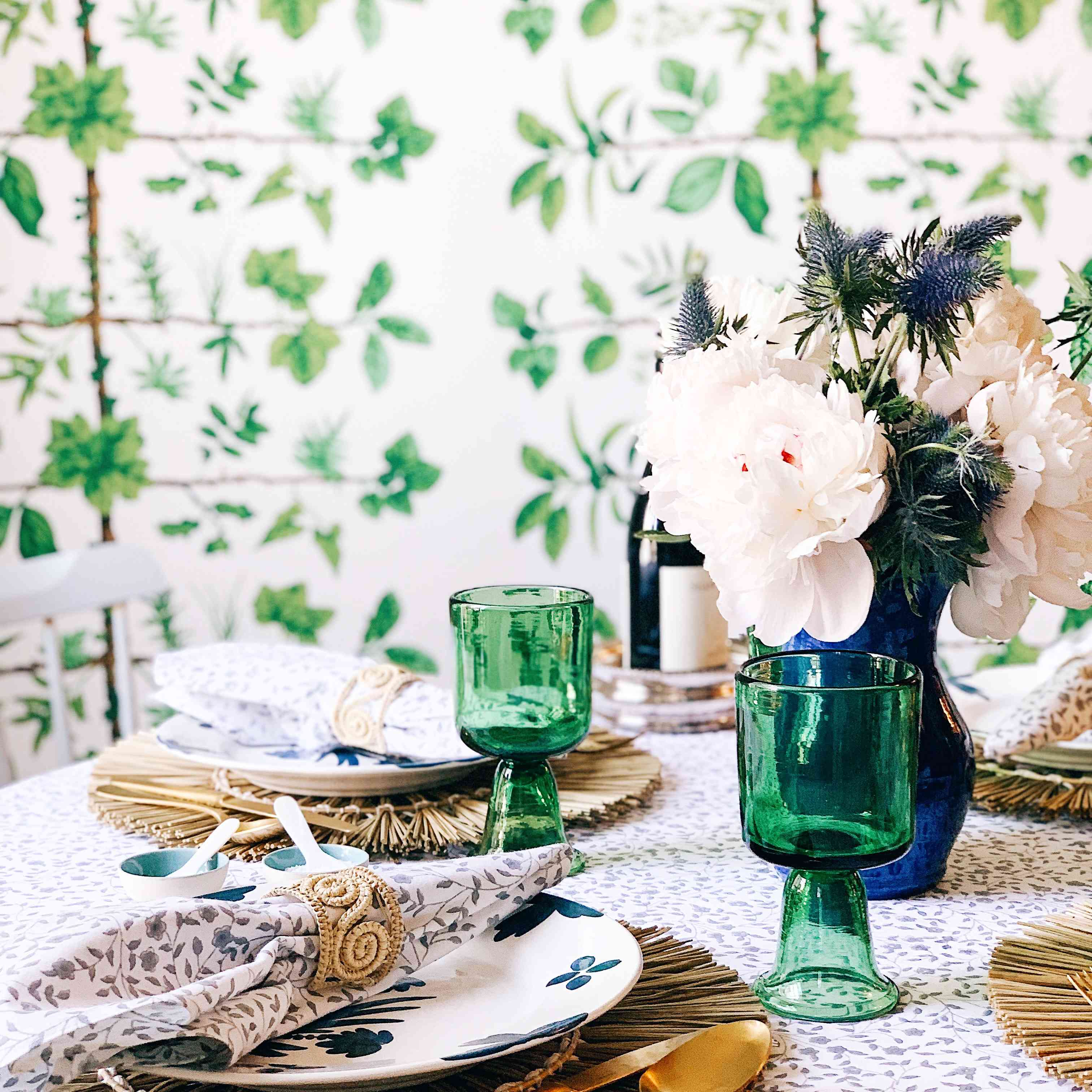 tablesetting features matching chargers, plates, green glasses, and white florals for the centerpiece