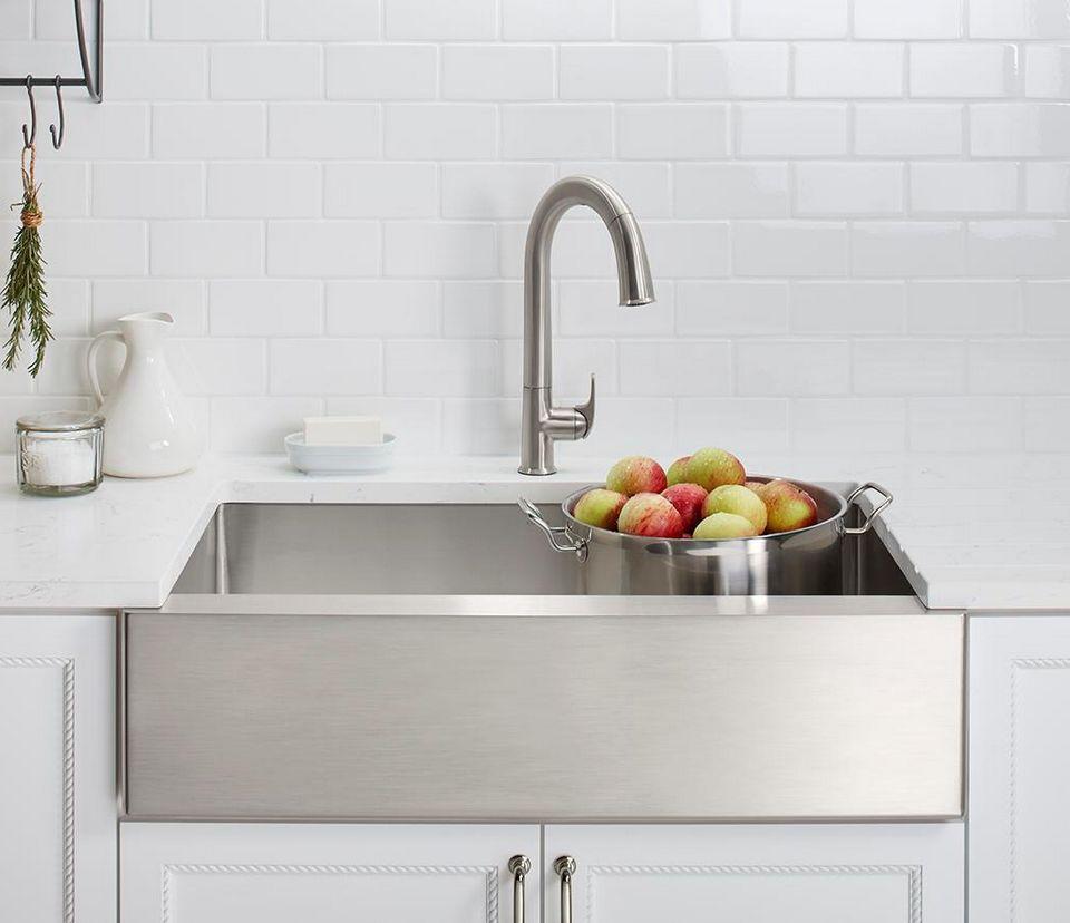 Fregadero de delantal de acero inoxidable Kohler Strive con una olla de manzanas en una cocina blanca