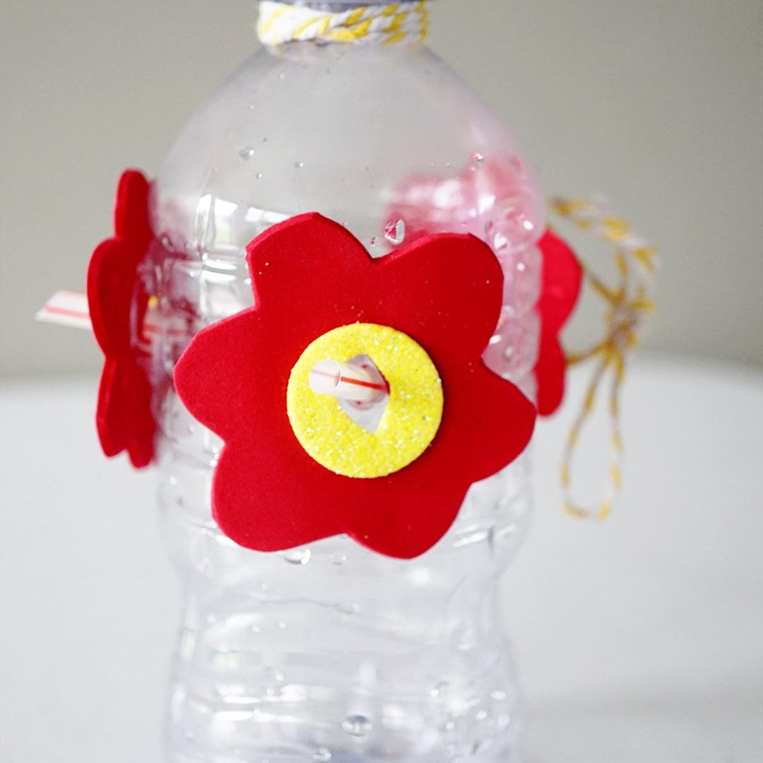 A plastic bottle with red and yellow foam flowers