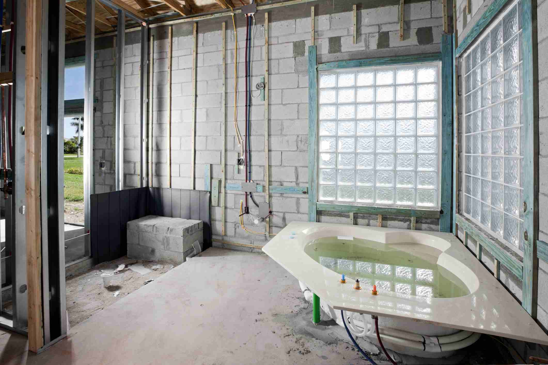 Bathroom with jacuzzi being constructed with glass block wall