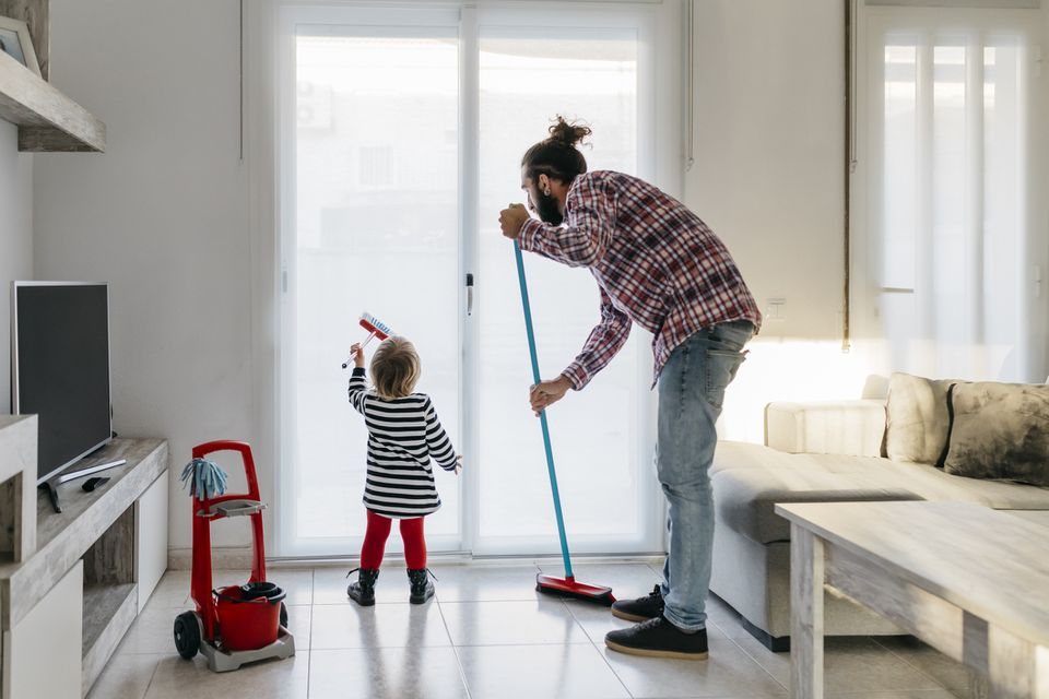Father and young daughter cleaning living room