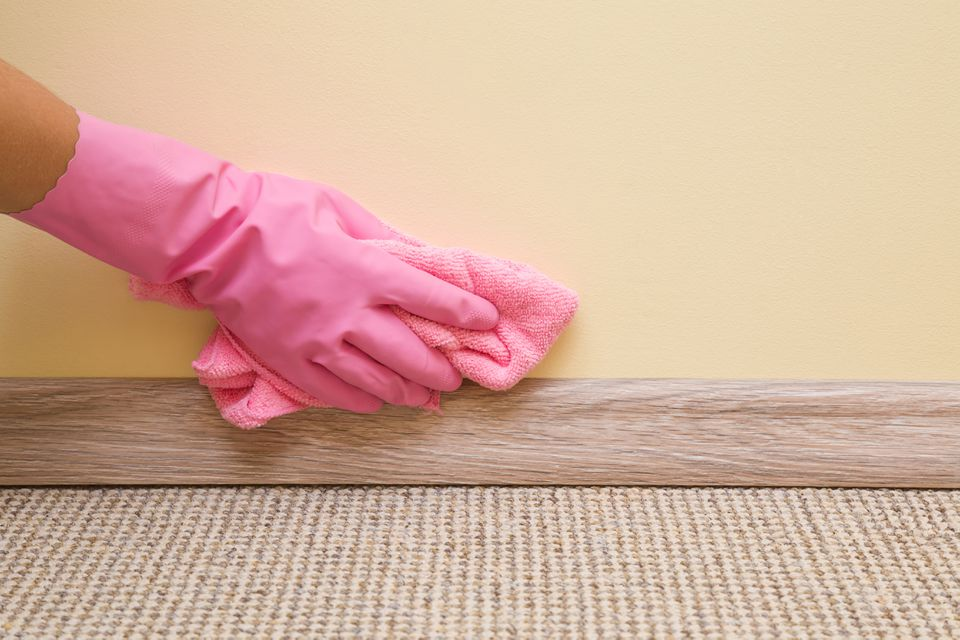Pink-gloved hand dusting wall and base board