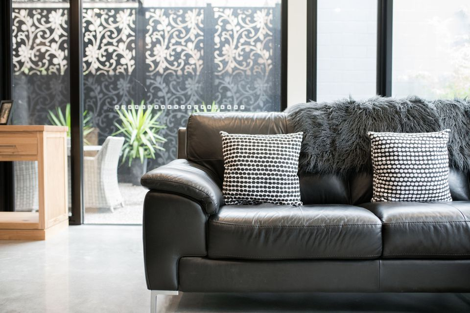 Leather couch with two black-and-white pillows.
