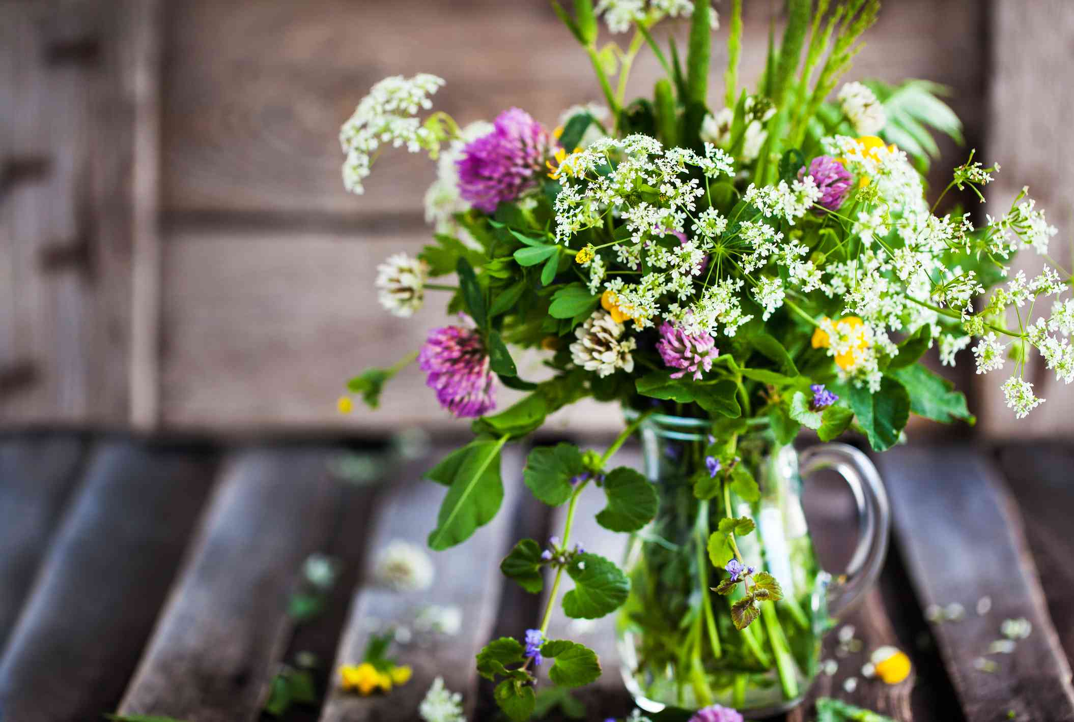 Bouquet of wildflowers in glass jar on wooden table