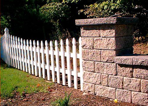 Photo of masonry fence and picket fence joined.