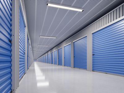 an inside hallway of a self-storage facility with grey floors and blue doors