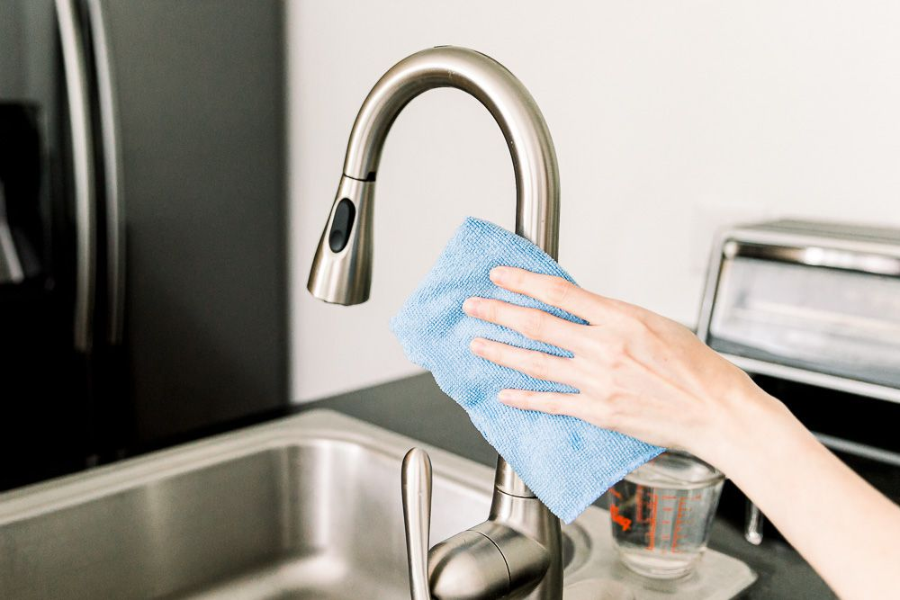 wiping down stainless steel with a microfiber cloth