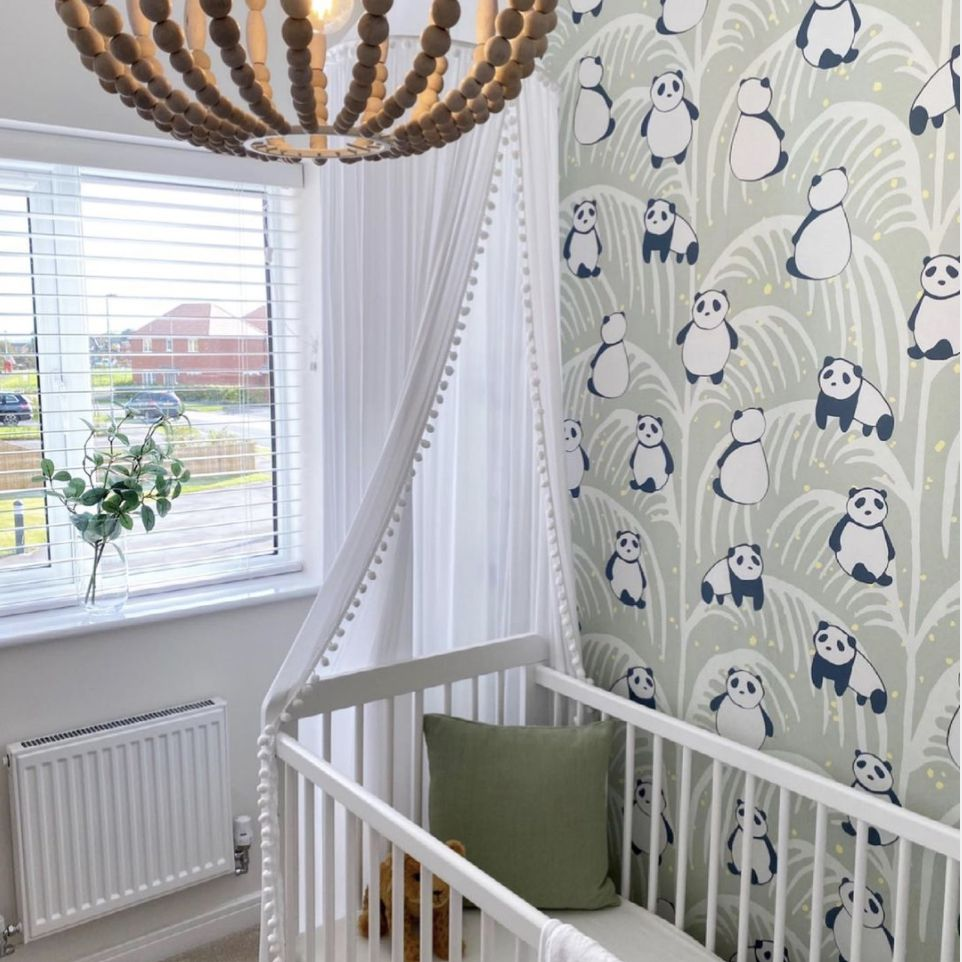nursery with green panda wallpaper and white accents
