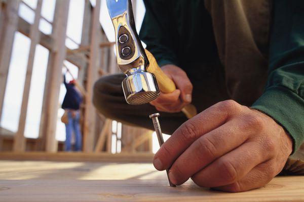 Hitting nail into wooden beam